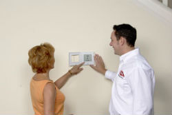 technician explaining thermostat to homeowner