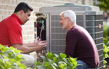 HVAC repair technician discussing air conditioner repair with homeowner
